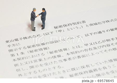 秘密保持契約書の上で握手しようとしているビジネスマンのミニチュア 69578645