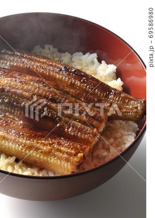 1匹分の鰻の蒲焼きが乗った出来立て鰻丼(白背景) 69586980