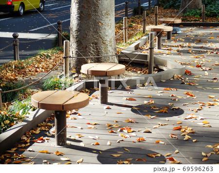 落ち葉散らばる定禅寺通遊歩道のウッドデッキの丸いベンチ 69596263