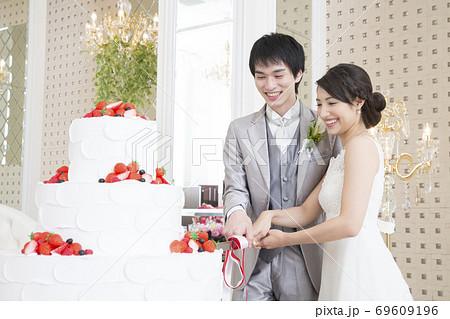 ケーキカットをする新郎新婦 69609196