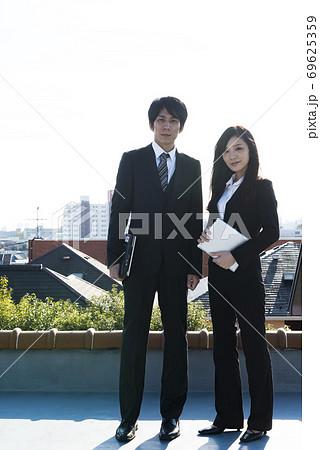住宅街をバックに立つビジネスウーマンとビジネスマン 東京 69625359