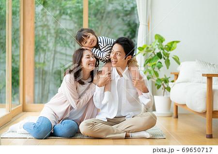 リビングの床でパパにおんぶされる女の子とママの3人家族のポートレート 69650717