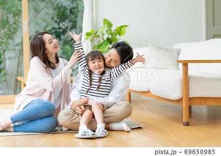 リビングの床に座ってはしゃぐ女の子とそれを見守るママとパパ 69650985
