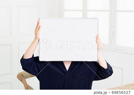 大きいスケッチブックを持つ若い女性 69656527