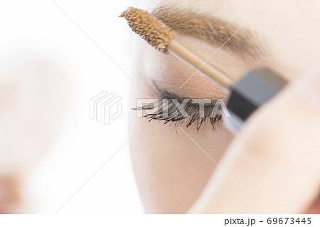 眉マスカラを塗る女性 69673445