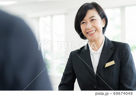 施設の案内をするスーツ姿のミドル女性 69674049