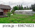 Photo of aged wooden house with glass greenhouse 69674823