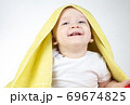 Happy eleven month old baby under yellow towel 69674825
