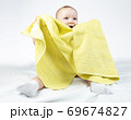 Photo of smiling eleven-month-old baby with yellow towel 69674827