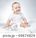 Photo of sitting eleven-month-old baby on a white background 69674829