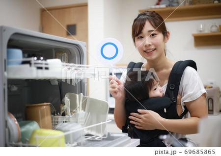 食器洗い機の前で〇の札を持つ女性 69685865