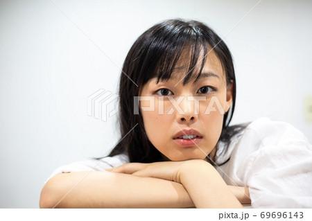 肘をついてまっすぐこちらを見る若い女性 69696143