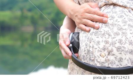 お腹にヘッドホンを当てて胎教をしている夫婦 69712423