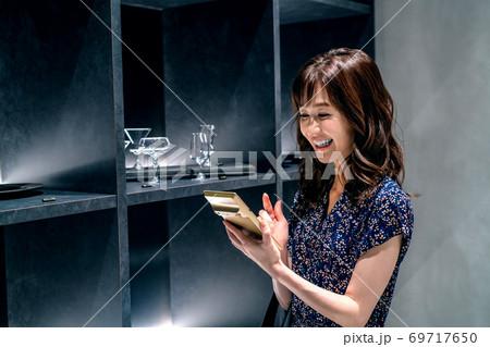店内で計算機を持ってお得をアピールする若い女性スタッフ 69717650