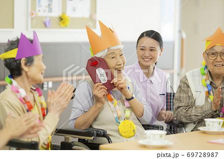 お誕生日会をするシニアの男女 介護施設 69728987