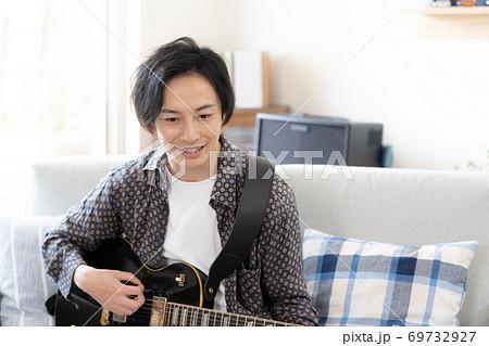 オンラインでバンド演奏をする男性【自宅】 69732927