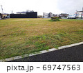 草刈りを終えた住宅街の空き地と草山、右側に停車するトラック 69747563