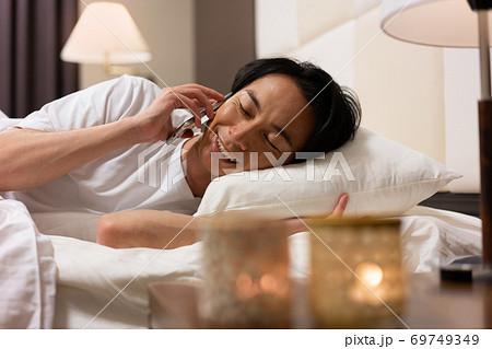 夜寝室で彼女と電話で話しをする若い男性 69749349