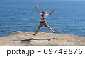 A fair-haired boy against the blue sea. 69749876