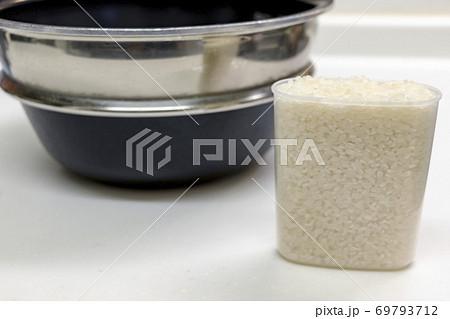 計量カップで量ったお米と炊飯器の釜 69793712