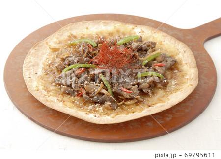 白バックに木製ピザ皿と焼肉クリスピーピザ 69795611