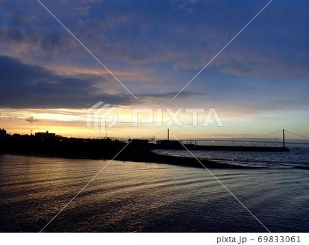 朝焼けでオレンジに照らされた海と明石海峡大橋 69833061