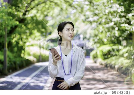 新緑の中スマホを使用している若い女性 69842382