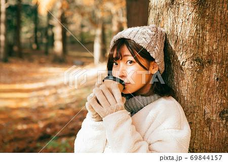 冬の屋外でホットコーヒーを飲む女性 69844157