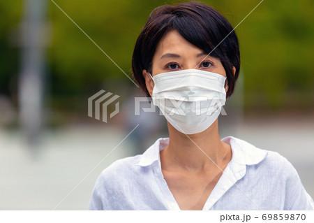 屋外でマスクをする女性(アップ) 69859870