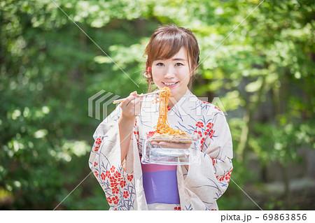 夏祭りで焼きそばを食べる浴衣姿の女性 69863856