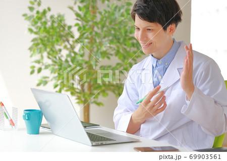 オンライン診療_左手を広げて説明する医師 69903561