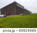 稲刈り前の稲穂たなびく田んぼの中に建築中の大型商業施設 69929989