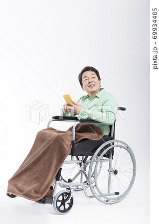 スマホを見る車椅子の男性 69934405