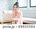 リビングでパソコンを使う若い女性 69935564
