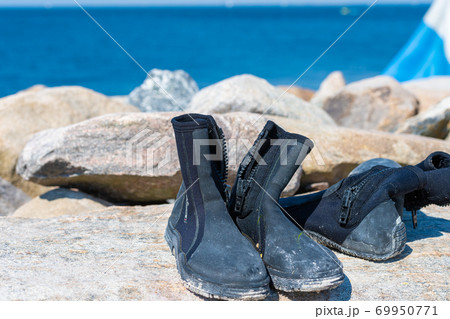 Dive boots drying on a stone. A dive flag and blue water in the background 69950771