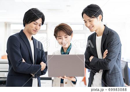 ノートパソコンを囲み談笑するビジネスイメージ 69983088
