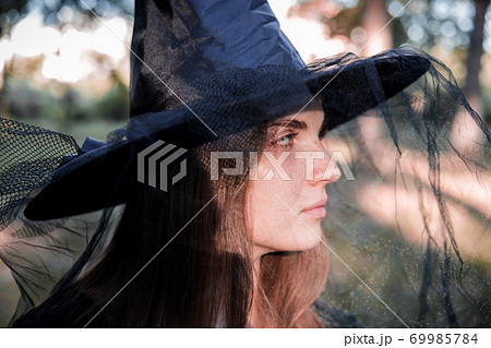 Pretty young beautiful woman in dark dress and witch hat standing in the middle of the autumn woods or park. Halloween party costume. Close-up portrait. Shadow on her face. 69985784