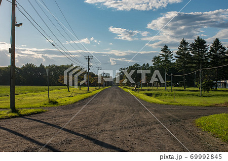 大自然をかける土の道と広大な青い空 69992845