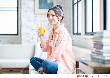 リビングでオレンジジュースを飲む若い女性 70010773