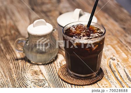 アイスコーヒーとガムシロップと砂糖の置かれた木目調のテーブル 70028688