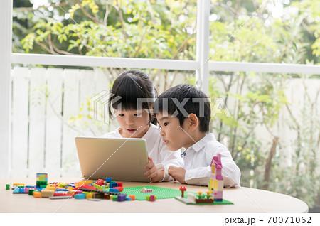 タブレットでブロックの作り方を調べる姉弟 70071062