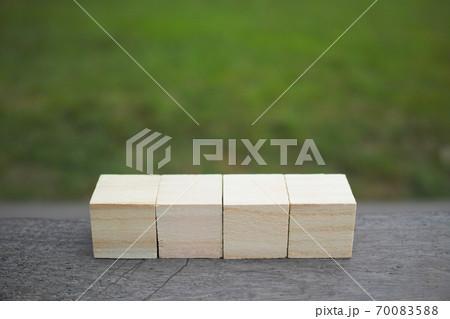 テーブルの上に置いた4個の木製キューブと緑の芝生の背景 70083588