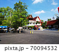 青空の下、駐車場の向こうに南国の大きな木とタイ様式の建築物の赤い屋根 70094532