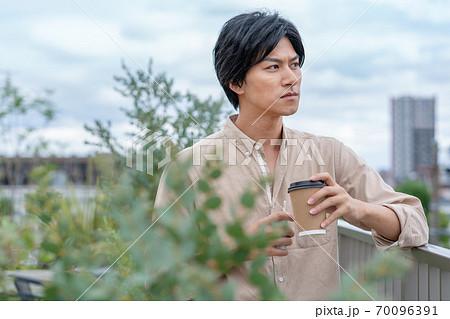 ビルの屋上で飲み物を飲みながら電子タバコをすう若い男性 70096391