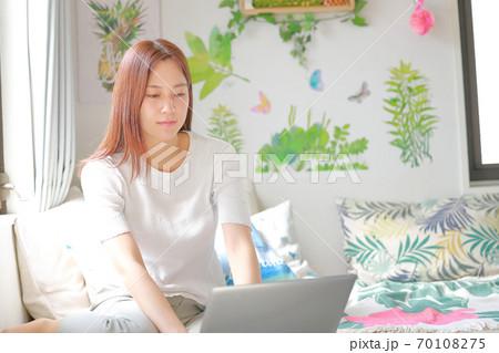 ソファーベッドに置いたPCを操作する女性 70108275