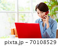 リビングでパソコンを使いながら電話をするミドル女性 70108529