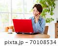 リビングでパソコンを使いながら電話をするミドル女性 70108534
