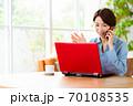 リビングでパソコンを使いながら電話をするミドル女性 70108535