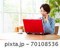 リビングでパソコンを使いながら電話をするミドル女性 70108536