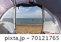 View through the open entrance to the tent on the sea. Sandy beach. 70121765